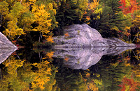 Mirror image featuring an interestingly shaped rock and the fall colors