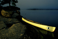 Canoe dramatically lit by a ray of sun on a misty morning