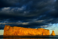 The Rocher Percé in Gaspésia is lit by the sunset light while a dark sky looks very threatening