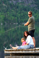 A couple with their daughter fish at the end of a dock